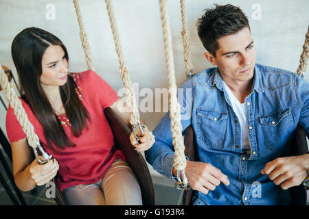Portrait of couple sitting in swings posing - Stock Photo