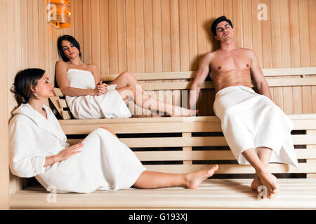 Group of young healthy, fit and beautiful people relaxing in a sauna - Stock Photo