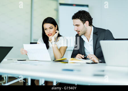 Young, successful businesswoman and a businessman looking at a paper while sitting at a office desk - Stock Photo