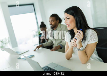 Young and beautiful businesswoman sitting at an office desk with colleagues - Stock Photo