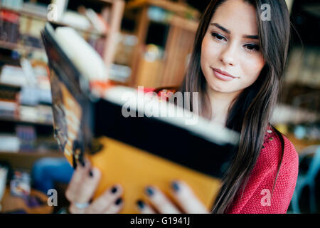 Beautiful woman reading book and preparing for exam - Stock Photo