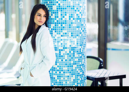 Portrait of a beautiful young woman in a bathrobe next to a swimming pool - Stock Photo