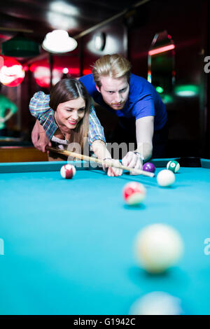 Young handsome man and woman flirting while playing billiard - Stock Photo