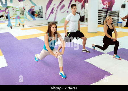 People exercising in fitness club with the help of personal trainer - Stock Photo