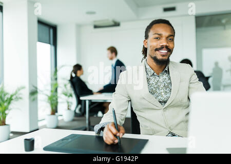 Black handsome graphics designer  with dreadlocks using digitizer in a well lit, tidy office environment  while - Stock Photo