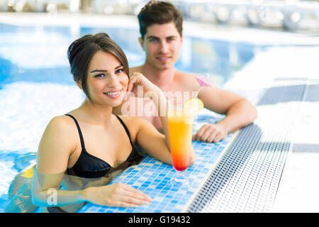 Couple drinking a cocktail by the swimming pool and relaxing - Stock Photo