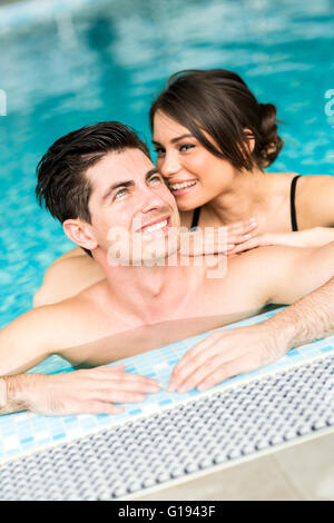Couple in love relaxing by the side of the swimming pool - Stock Photo