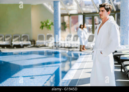 Man standing next to a  pool in a  robe and relaxing - Stock Photo