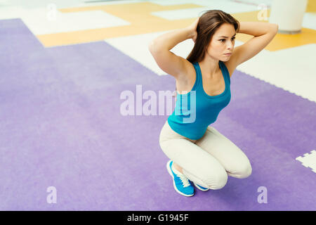 Beautiful woman stretching and exercising in beautiful room - Stock Photo