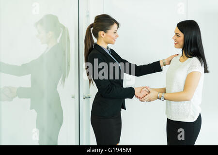 Handshake between two colleagues in a business office - Stock Photo