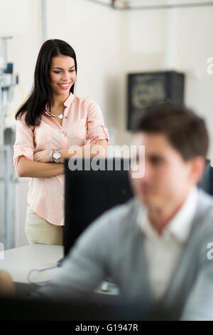 Beautiful young female teacher overseeing students' work in a classrom equipped with computers - Stock Photo