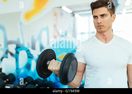 Handsome man lifting weights in gym and staying fit - Stock Photo