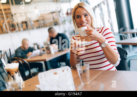 Beautiful woman enjoying beverages in nice cafe - Stock Photo