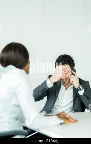 Businessman receiving bad news on the phone having a headache over the problems - Stock Photo