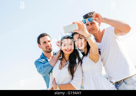 Group of cheerful and beautiful young people taking selfies of themselves - Stock Photo