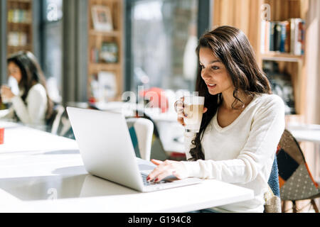 Beautiful brunette enjoying coffee and using laptop - Stock Photo