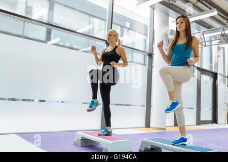 Beautiful women exercising aerobics in nice fitness club - Stock Photo