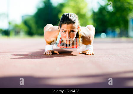 Focused young beautiful woman doing push-ups outdoors on a hot summer day - Stock Photo