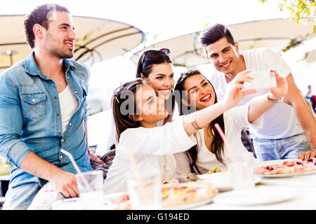 Group of young beautiful people sitting in a restaurant and taking a selfie while smiling - Stock Photo