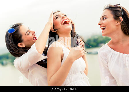 Cheerful women having fun outdoors and laughing happily - Stock Photo