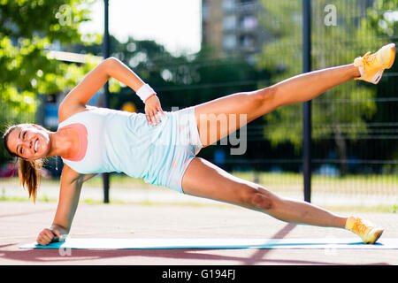 Beautiful woman doing exercises outdoors on a sunny day - Stock Photo