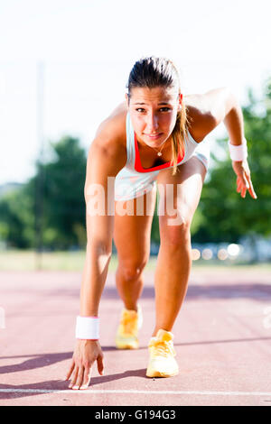 Beautiful female sprinter getting ready for the run during summer - Stock Photo