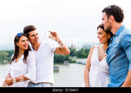 Young and beautiful couples taking photos with smartphone - Stock Photo