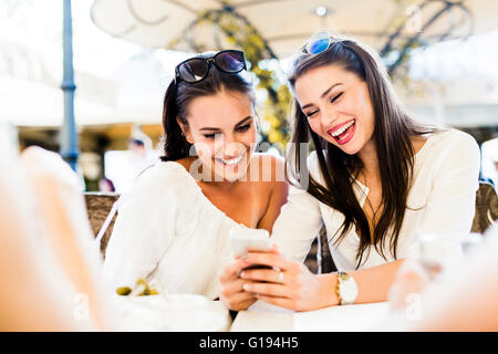 Two young girls talking and smiling during lunch break - Stock Photo