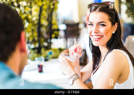 Beautiful young woman sitting at a table outdoors and drinking a beverage - Stock Photo