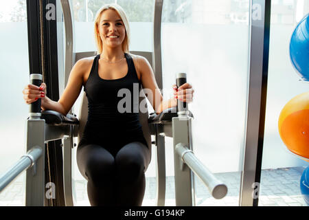 Beautiful woman training in gym and keeping body in shape - Stock Photo