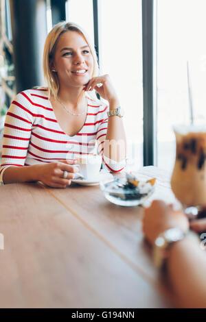 Beautiful women drinking coffee and gossiping in nice restaurant - Stock Photo