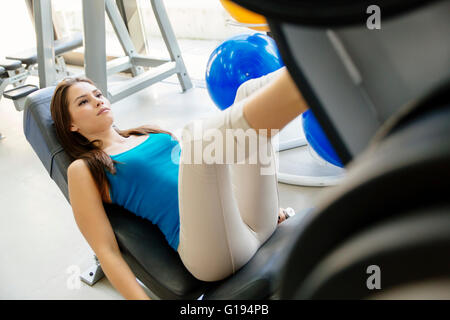 Woman working out in gym and training legs - Stock Photo