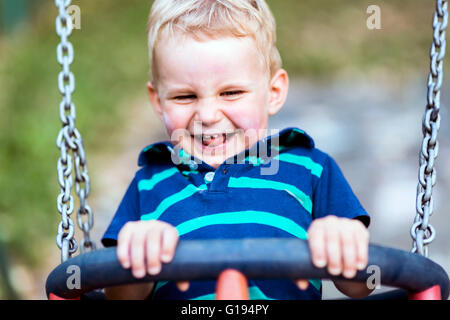 Playful child on swing outdoors smiling sincerely - Stock Photo
