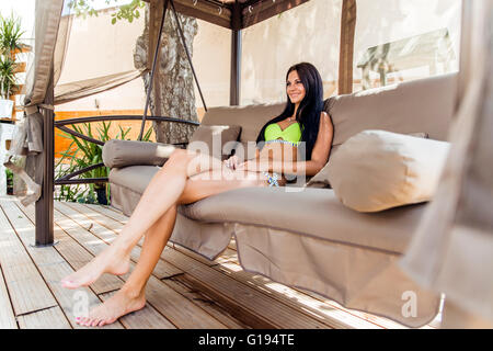 Beautiful young lady shading herself from sun in a big swing and relaxing - Stock Photo