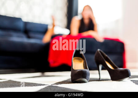 Closeup of high heels shoes in a hotel room and a woman in the background - Stock Photo