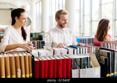 Group of students studying in library and reading books - Stock Photo