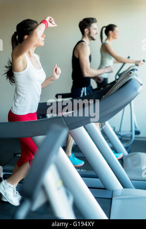 Young and beautiful  lady running on a treadmill and wiping sweat off her forhead - Stock Photo
