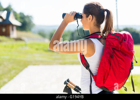 Portrait of a hiker woman using binoculars as she checks out the landscape - Stock Photo