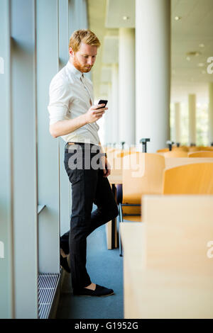 Relaxed businessman having a break and looking at his phone - Stock Photo