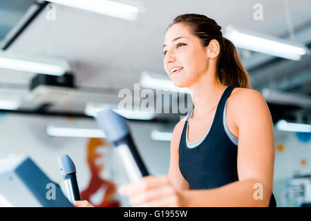 Beautiful young lady using the elliptical trainer in a gym in a positive mood - Stock Photo