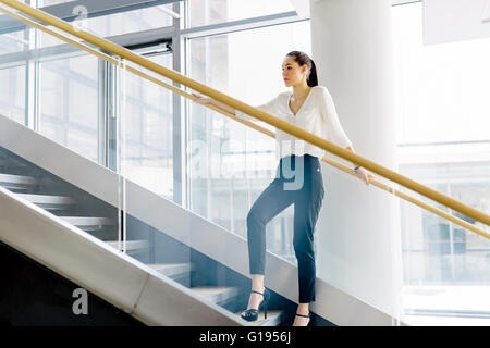 Businesswoman on stairs in a modern office - Stock Photo