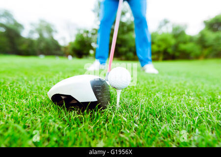 Golfer getting ready to take a shot. Wide angle photo and closeup - Stock Photo