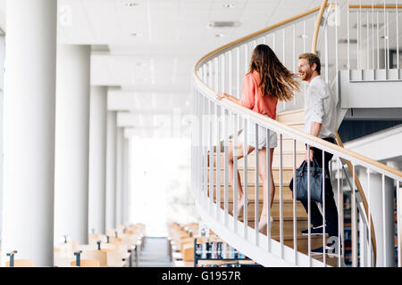 Beautiful businesswoman handsome businessman climbing stairs in a beautiful environment - Stock Photo