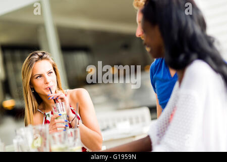 Beautiful woman sipping through a straw outdoors while sitting at a table - Stock Photo