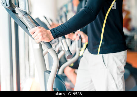 Young healthy group of people working out on a elliptic trainer in a fitness center - Stock Photo