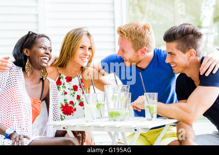 Friends laughing and hugging each outher outdoors and being happy - Stock Photo