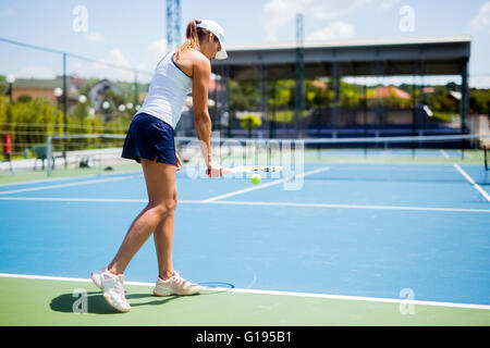 Beautiful female tennis player serving outdoor - Stock Photo