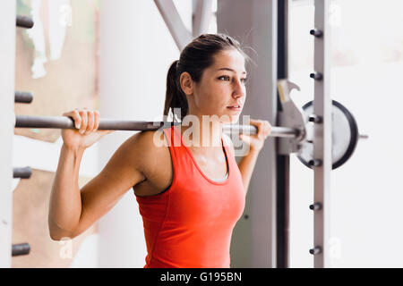 Focused young beautiful woman lifting weights in a gym - Stock Photo
