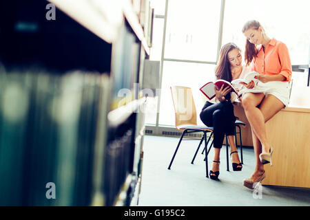 Two beautiful students studying in the library and reading books - Stock Photo