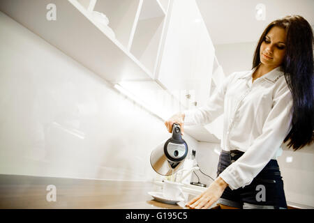 Closeup of hot water being poured out of the kettle in a modern kitchen - Stock Photo